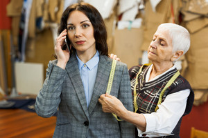 Businesswoman speaking on mobile telephone while clothier taking measures of her jacket