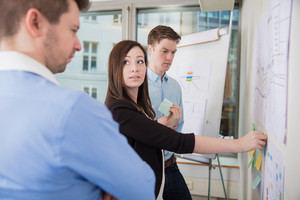 Businesswoman Sticking Adhesive Notes While Looking At Male Coll