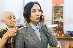 Businesswoman talking on cellphone while clothier taking measures of her shoulder