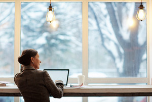 Businesswoman with laptop looking through window while spending time in cafe