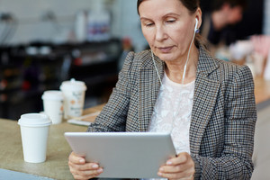 Businesswoman with touchpad watching and listening to information in the net