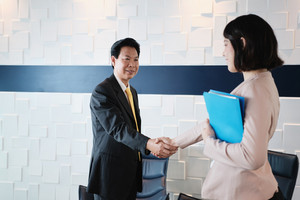 Businesswoman working as advisor in office, financial consultant with papers and customer. Health insurance broker meeting Chinese manager, retirement plan agent shaking hands with businessman