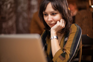 Businesswoman working on her laptop in a coffee shop. Charming woman. Freelancer at work.