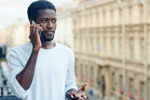 Busy guy in homewear speaking on smartphone on balcony