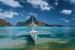 Cadlao panorama with Traditional filippino banca boat in front. Exotic tropical El Nido bay, Palawan Island, Philippines