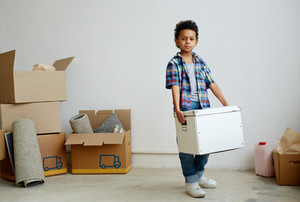 Calm boy holding packed box while looking at camera