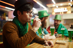Calm guy in hat drinking beer from glass