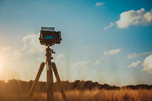 camera on tripod in wheat field, silhouette on sunset sky with whie moving clouds in background