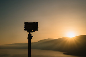 Camera on tripod Photographer takes amazing sunrise above the mountain peaks and calm sea bay.