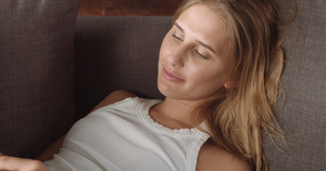 Camera starts with a pretty girl on the couch reading something on her tablet and goes off to industrial grey floor
