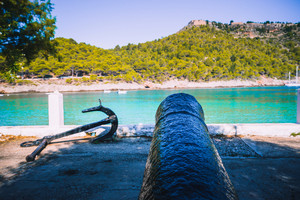 Cannon and anchor on coast of Kefalonia island in Assos village. Tranquil sea bay and lush pine grove. Greece