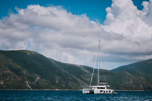 Catamaran ship in open sea near Fiskardo. Big clouds moving over the mountain shape of Ithaki island. Kefalonia Island Greece
