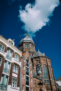 Cathedral in Amsterdam against blue sky and white cloud. Low angle view