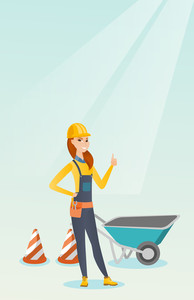 Caucasian builder showing thumb up while standing near wheelbarrow. Young builder in hard hat giving thumb up. Builder at work on construction site. Vector flat design illustration. Vertical layout.