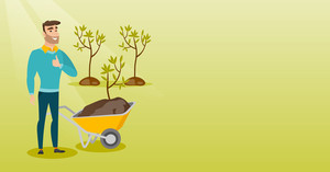 Caucasian gardener with wheelbarrow standing on the background of newly planted trees. Young gardener pushing wheelbarrow with tree and dirt in park. Vector flat design illustration. Horizontal layout