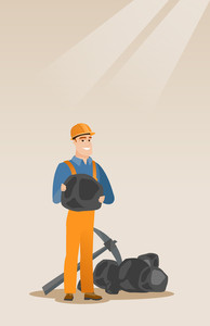 Caucasian male miner in hard hat holding coal in hands. Young miner with a pickaxe. Miner working at coal mine. Young happy male miner at work. Vector flat design illustration. Vertical layout.
