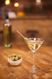 Celebration with a glass of white martini and olives in a restaurant at the bar counter. Club drink. Fresh drink.