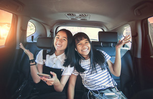 cheerful asian teenager happiness emotion sitting in passenger car