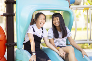 cheerful asian teenager laughing in children playground