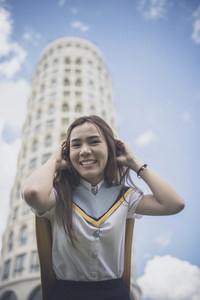 cheerful asian younger woman wearing university uniform pose street fashion style