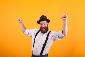 Cheerful bearded man rising up his fists and looking at the camera over yellow background.