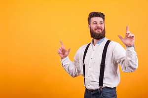 Cheerful bearded man smiling and pointing up over yellow background.