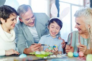 Cheerful boy with bunny ears, his parents and grandmother painting eggs for Easter