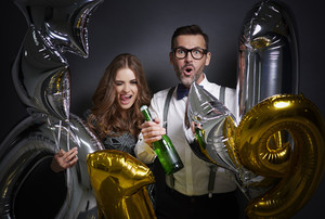 Cheerful couple with champagne and ballons celebrating