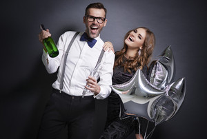 Cheerful couple with champagne celebrating new year