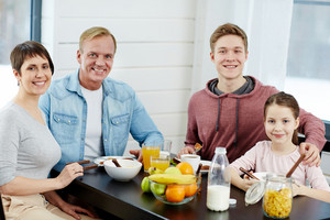 Cheerful family sitting by table with healthy organic food