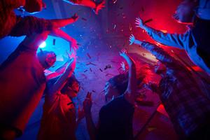 Cheerful friends dancing at xmas party