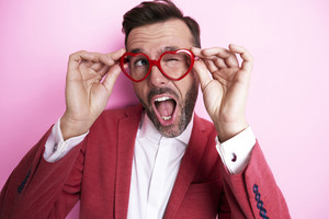 Cheerful man trying heart shape eyeglasses