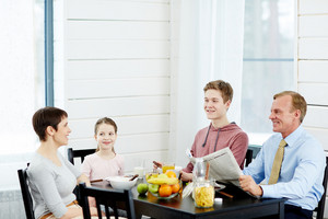 Cheerful modern family of four enjoying each others company while sitting in kitchen and eating healthy breakfast, waist-up portrait