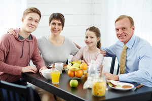 Cheerful parents and kids sitting by table in the kitchen