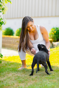 Cheerful pregnant woman with a big belly plays with her dog in the garden