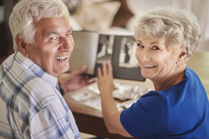 Cheerful senior couple browsing album with their photographs