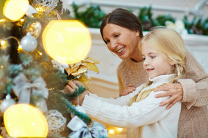 Cheerful woman and girl hanging decorative toys on xmas tree