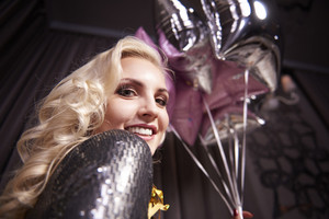 Cheerful woman holding bunch of balloon at night club