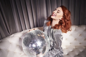 Cheerful woman holding disco ball