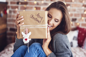 Cheerful woman sitting on bed and holding a gift