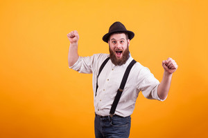 Cheerful young bearded man wearing a hat and smiling looking at the camera over yellow background. Stylish beard.
