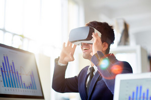 Cheerful young businessman in stylish suit using VR headset while sitting at desk in modern open plan office, lens flare