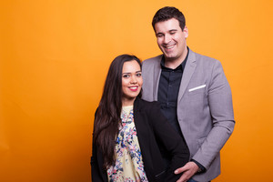 Cheerful young couple smiling over yellow background. Beautiful relationship. Attractive man and woman.