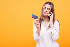 Cherful young girl wearing white shirt talking on the phone and holding credit card. Good conversation