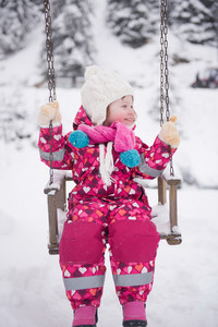 child outdoor in park at winter day with fresh snow, cute little girl swing and playing