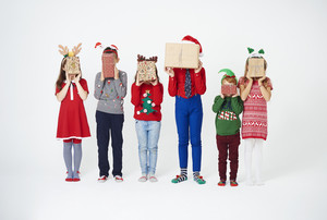 Children holding christmas present in front of their face