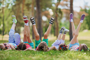 Children lying on green grass in park on a summer day with their legs lifted up to the sky