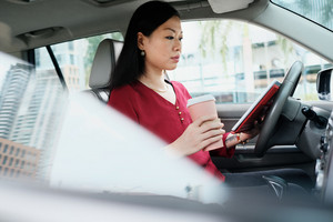 Chinese female manager working in car. Successful Asian businesswoman using laptop computer for Internet. Busy woman sitting in car and drinking coffee