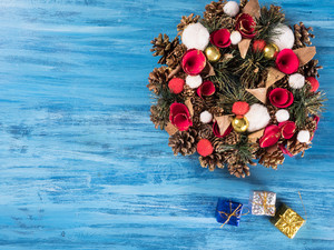 Chistmas door decoration with small gift boxes on blue wooden background. Greeting symbol.