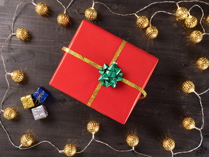 Christmas gift box on wooden background with small presents and Christmas light. Happy winter holidays.